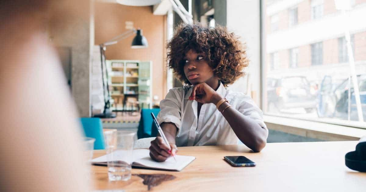 an image of a curly haired girl studying at a table