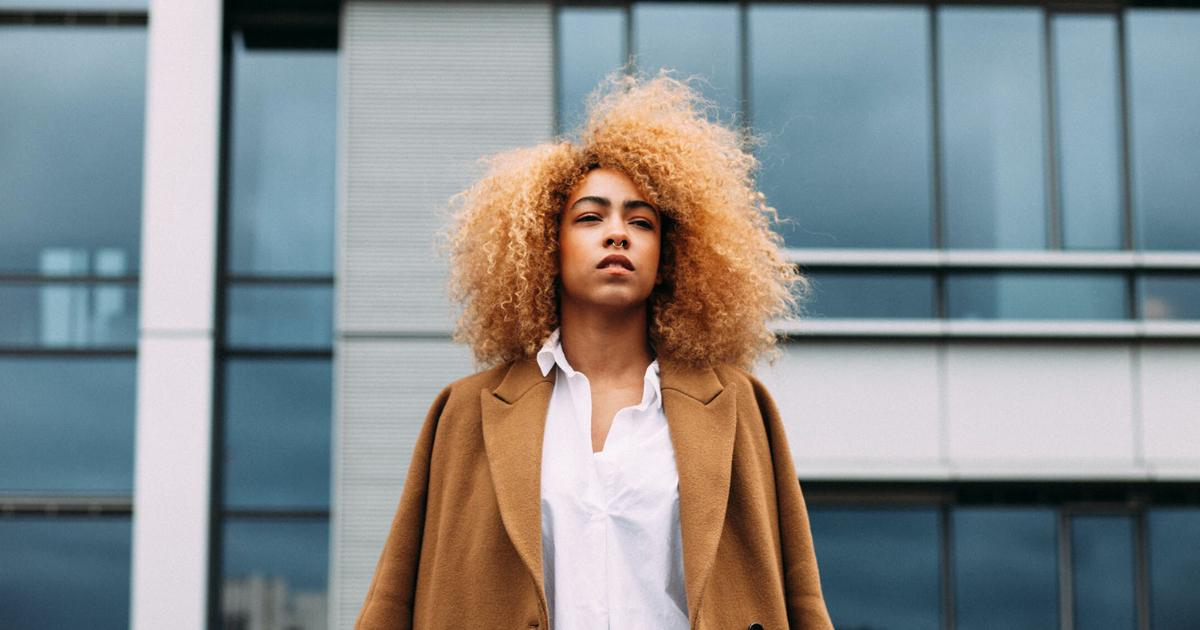an image of a black girl with blonde curly hair wearing a jacket showing winter natural hair routine