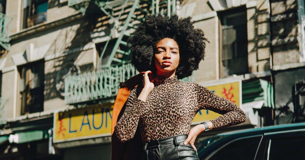 an image of a girl with fine type 4 natural hair against a street backdrop