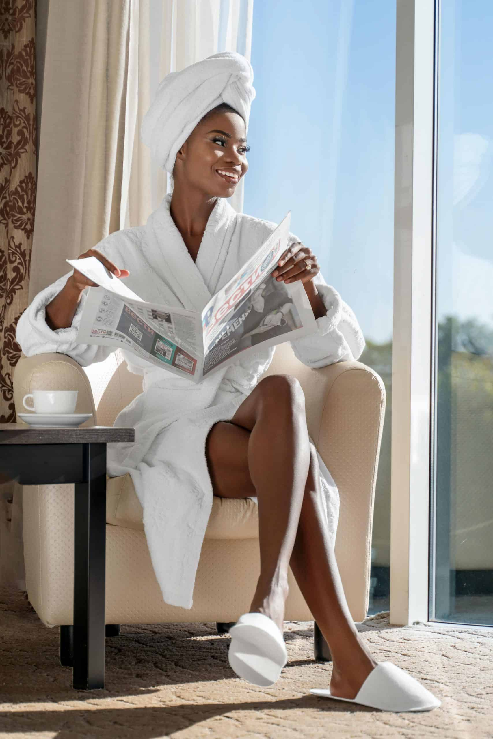 an image of a black woman sitting in a chair with a newspaper having wash day